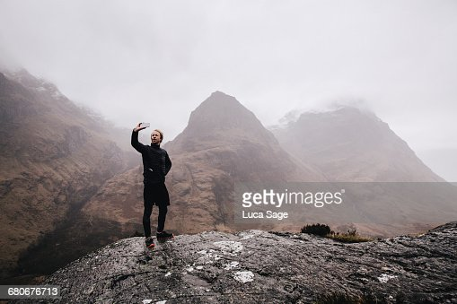 A runner takes a selfie on a mountain in Scotland : Stock Photo