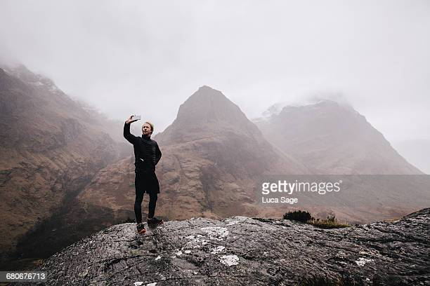 A runner takes a selfie on a mountain in Scotland