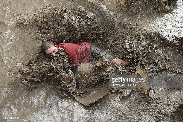 TOPSHOT A runner takes part in the Mud Day a 13km obstacle race on October 1 2016 in Merignac southwestern France / AFP / NICOLAS TUCAT