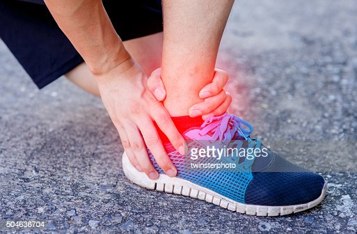 Runner touching painful twisted or broken ankle. Runner training accident : Stock Photo