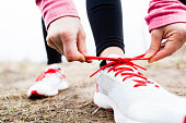 Woman runner tying sport shoes. Walking or running legs, autumn adventure and exercising outdoors.