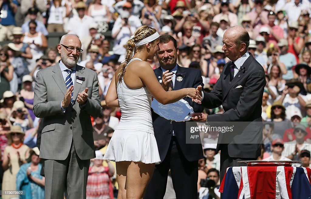 Runner up Germany's Sabine Lisicki shakes hands with Prince Edward, Duke of Kent (R) during the presentation after losing the women's singles final match to France's Marion Bartoli on day twelve of the 2013 Wimbledon Championships tennis tournament at the All England Club in Wimbledon, southwest London, on July 6, 2013. Bartoli won 6-1, 6-4.