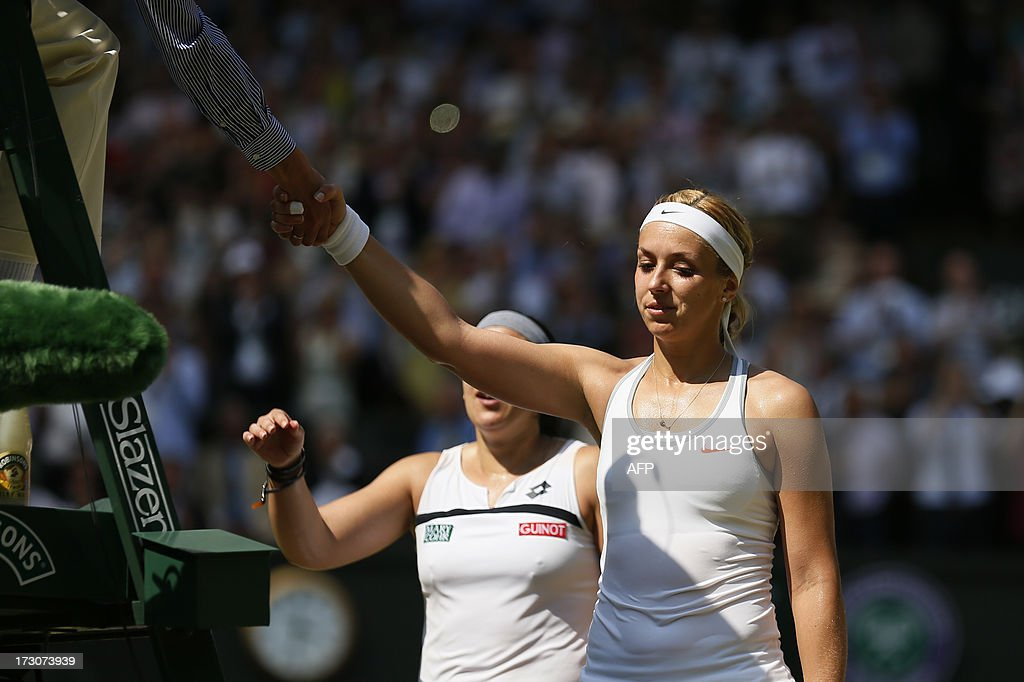 Runner up Germany's Sabine Lisicki (R) shakes hands with the umpire after losing the women's singles final match to France's Marion Bartoli (L) on day twelve of the 2013 Wimbledon Championships tennis tournament at the All England Club in Wimbledon, southwest London, on July 6, 2013. Bartoli won 6-1, 6-4.