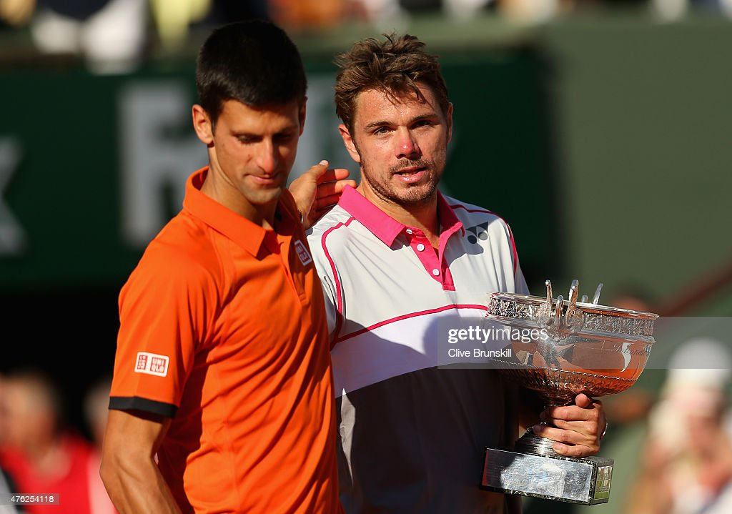 Runner up Novak Djokovic of Serbia leaves the podium as Stanislas Wawrinka of Switzerland poses with the Coupe de Mousquetaires after their Men's...