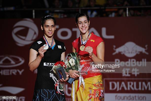 Runner up Saina Nehwal of India and winner Carolina Marin of Spain celebrate on the podium in the women singles awarding ceremony of the 2015 Total...