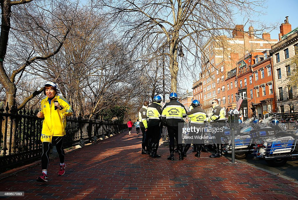 A runner warms up near a group of Boston Police officers prior to the start of the 2014 B.A.A. 5K on April 19, 2014 in Boston, Massachusetts.