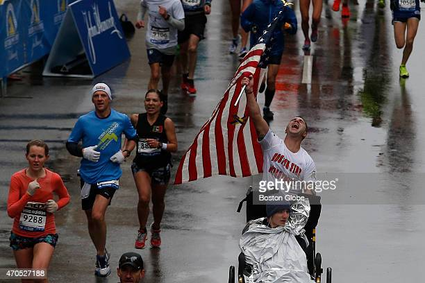 A runner wearing a Boston Fire Department shirt and pushing a man in a wheelchair raises up an American flag before crossing the the 119th Boston...