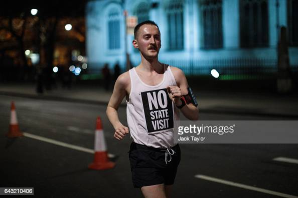 A runner wearing a vest which reads 'No State Visit' jogs around Parliament Square as thousands rally against US President Donald Trump's state visit...