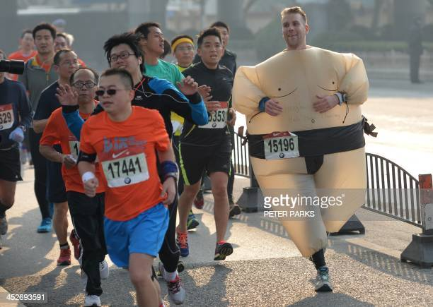 A runner wears a Sumo suit whilst running in a marathon in Shanghai on December 1 2013 Around 3000 runners took part in the annual event AFP...