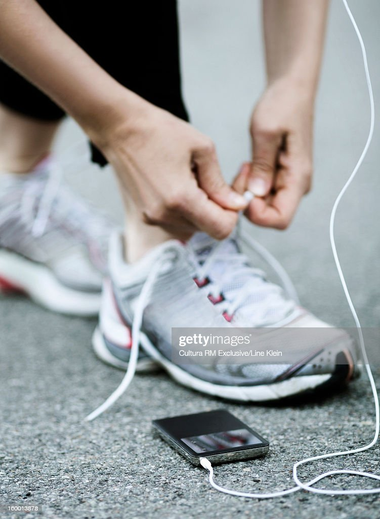 Runner with headphones tying her shoes : Stock Photo