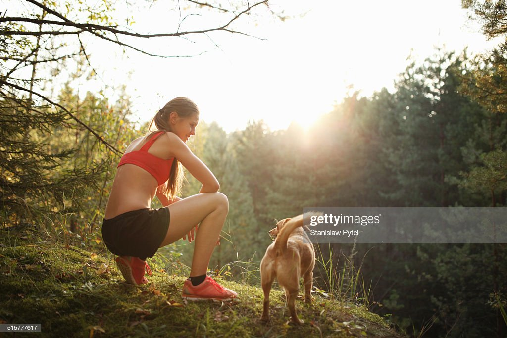 Runner with her dog at scenic overlook in forest : Stock Photo