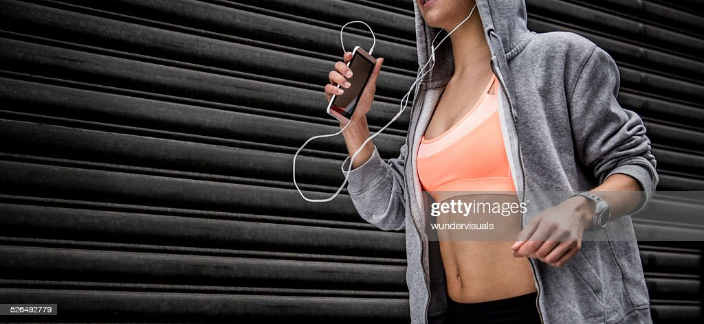 Runner With Smartphone In Hand and Listening To Music
