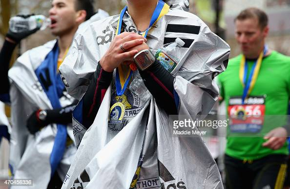 A runner wrapped in a heat blanket walks down Boylston Street following the 119th Boston Marathon on April 20 2015 in Boston Massachusetts