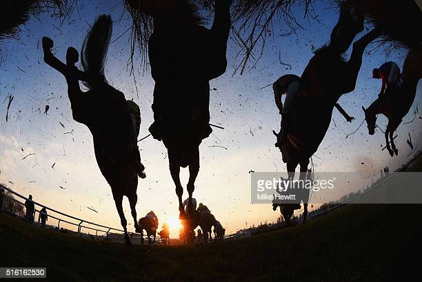 Runners and riders clear a jump in the Fulke Walwyn Kim Muir Challenge Cup Handicap Chaseon day three St Patrick's Thursday of the Cheltenham...