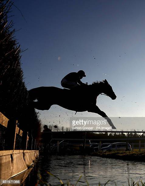 Runners and Riders jump the open ditch during The Betfred 'Treble Odds On All Lucky 15's' Handicap Steeplechase at Newbury Racecourse
