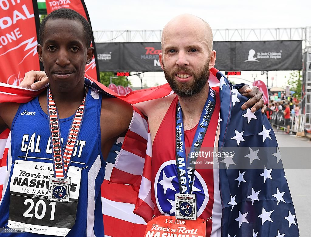 Runners and winners of half-marathon and marathons, Roosevelt Cook and Scott Wietecha celebrate as they cross the finish-line in the St. Jude Rock 'n' Roll Nashville Marathon/Half Marathon and 5k where more than 34,000 participants weathered the rain during the 17th running on April 30, 2016 in Nashville, Tennessee.