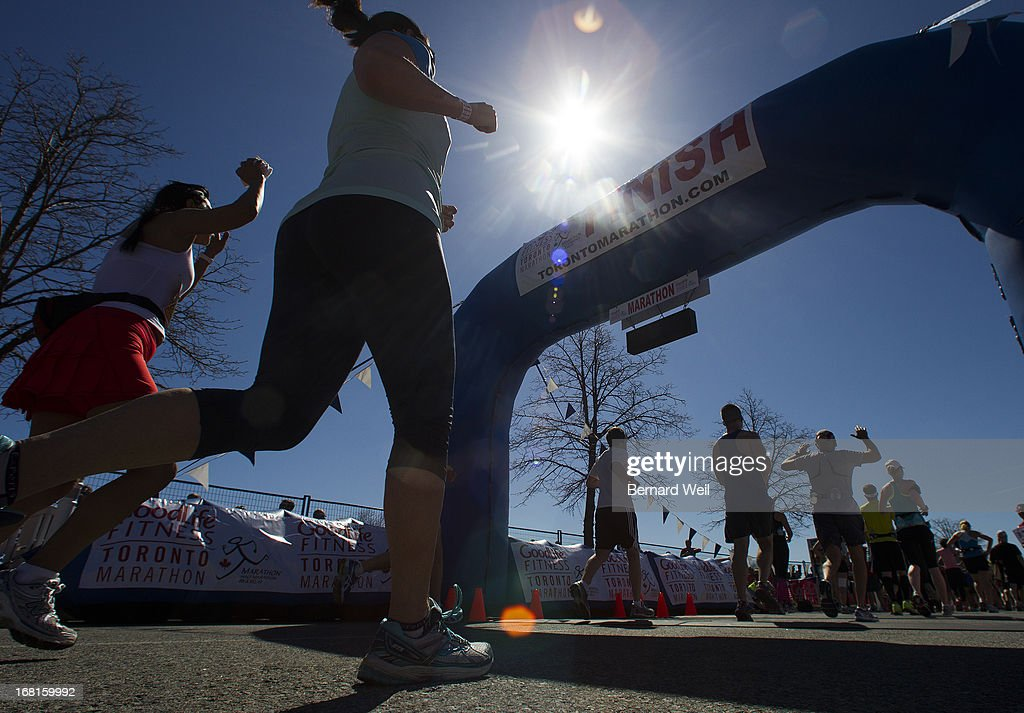 Runners are silhouetted against the sun as they cross the finish line in the Toronto Marathon.