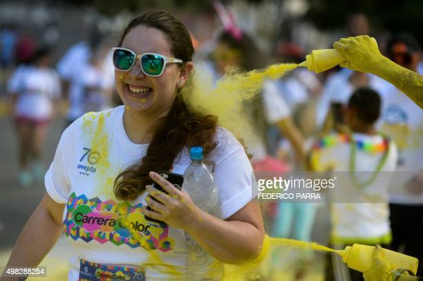 Runners are 'sprayed' with coloured powder during the Color Run in Caracas on November 22 2015 AFP PHOTO/FEDERICO PARRA