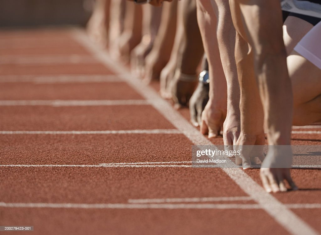 Runners at start of race, hands behind start line, low section : Foto de stock