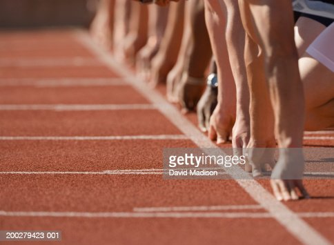 Runners at start of race, hands behind start line, low section : Stock Photo