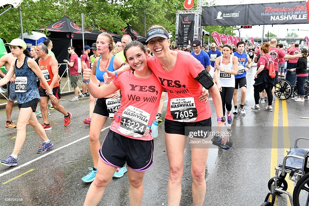 Runners Avery Cheves and Tina Clossick cross the finish line at the St. Jude Rock 'n' Roll Nashville Marathon/Half Marathon and 5k where more than 34,000 participants weathered the rain during the 17th running on April 30, 2016 in Nashville, Tennessee.
