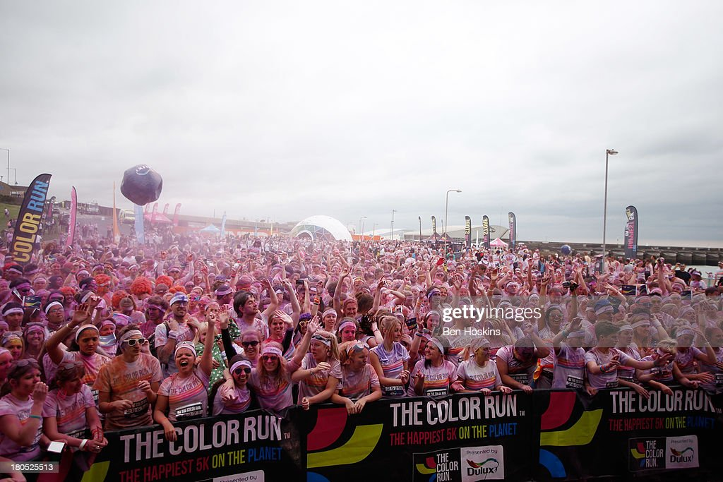 Runners celebrate after taking part in The Color Run presented by Dulux, known as the happiest 5km on the planet on September 14, 2013 in Brighton, England. Runners of all shapes, sizes and speeds start wearing white clothing that is a blank canvas for the kaleidoscope of colours they encounter around The Color Run course. At each kilometre a different colour of powder is thrown in the air with the runners becoming a constantly evolving artwork. At the end of the course runners are greeted by the Colour Festival where the air is filled with music and stunning coloured powder bursts creating a vibrant party atmosphere.