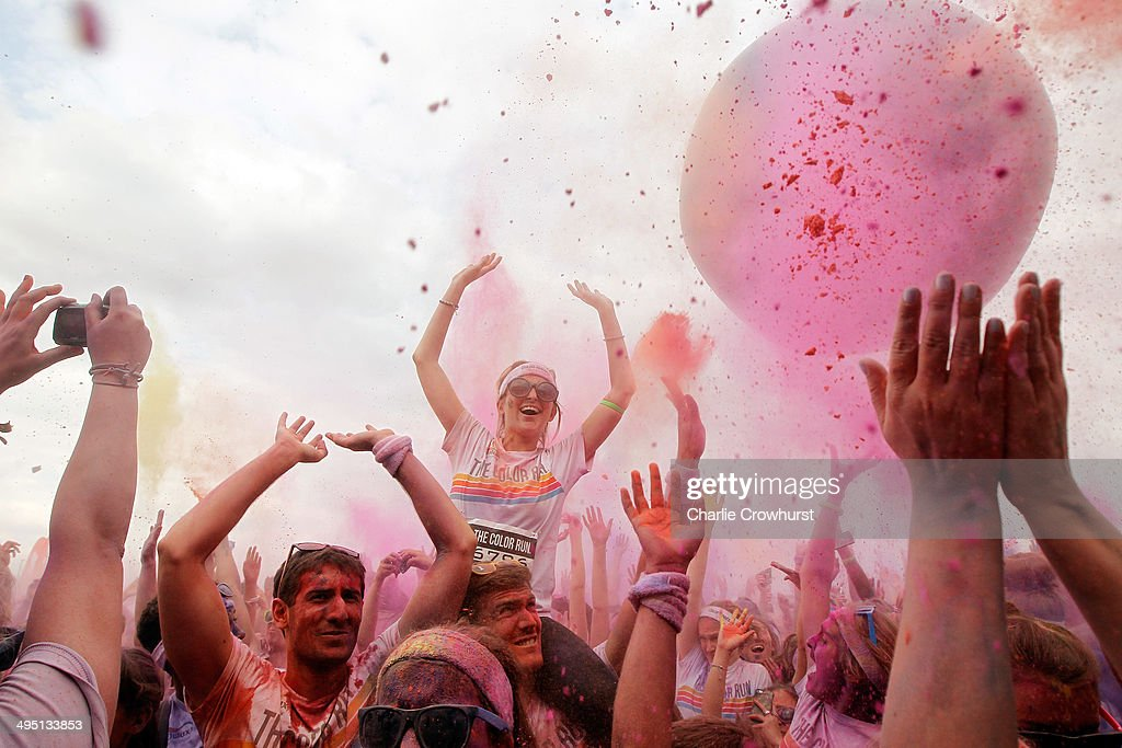 Runners celebrate in the Festival Area after the Color Run presented by Dulux, known as the happiest 5km on the planet on June 1, 2014 in London, England. Runners of all shapes, sizes and speeds start wearing white clothing that is a blank canvas for the kaleidoscope of colours they encounter around The Color Run course. At each kilometre a different colour of powder is thrown in the air with the runners becoming a constantly evolving artwork. At the end of the course runners are greeted by the Colour Festival where the air is filled with music and stunning coloured powder bursts creating a vibrant party atmosphere.