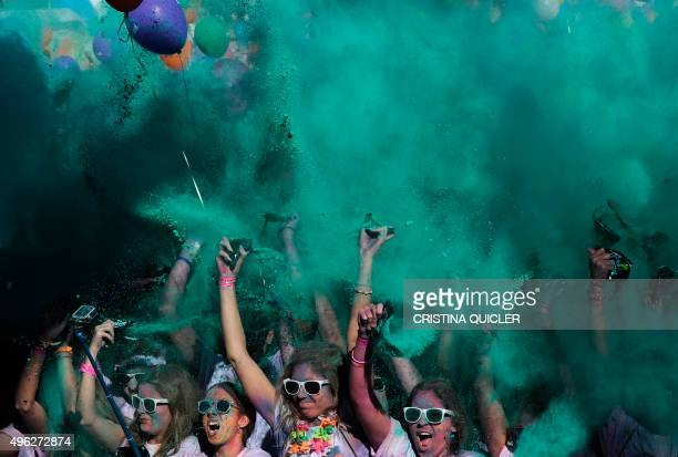 Runners covered in coloured powder dance after taking part in the Color Run of Sevilla on November 8 2015 The Color Run is a race where participants...