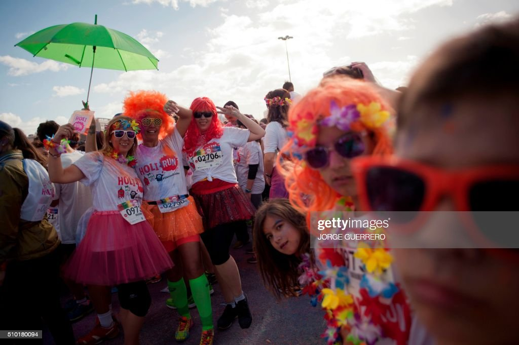 Runners covered in coloured powder dance during the Tour 2016 Holi Run Valentine Edition in Malaga on February 14, 2016. / AFP / JORGE GUERRERO