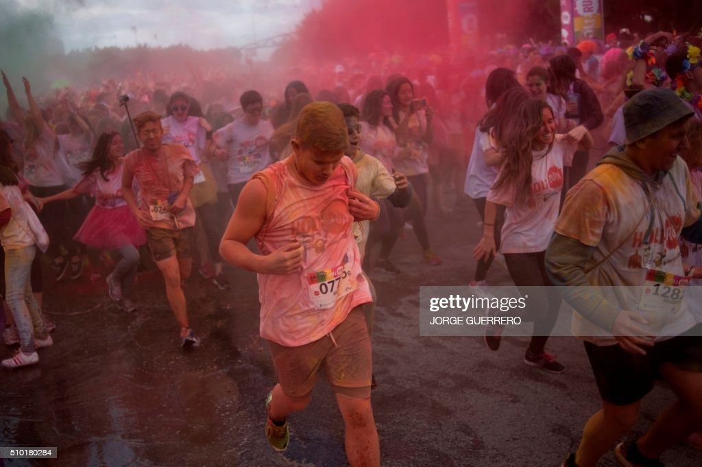 Runners covered in coloured powder run during the Tour 2016 Holi Run Valentine Edition in Malaga on February 14, 2016. / AFP / JORGE GUERRERO