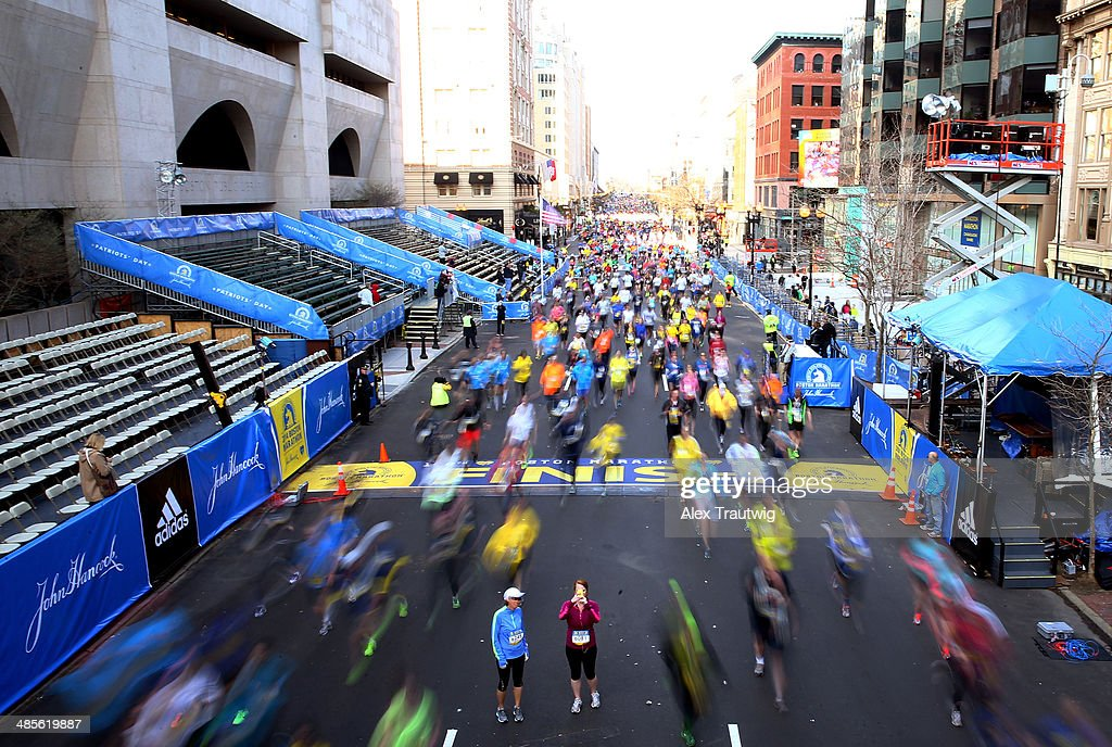 Runners cross the finish line of the Boston Marathon as part of the 2014 B.A.A. 5K race course on April 19, 2014 in Boston, Massachusetts.