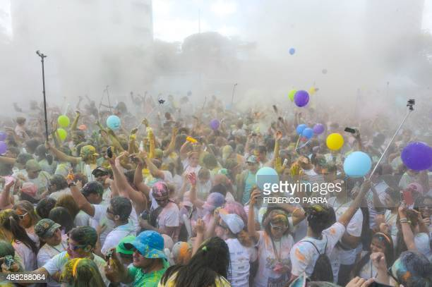 Runners dance covered in coloured powder after taking part in the Color Run of Caracas on November 22 2015 AFP PHOTO/FEDERICO PARRA