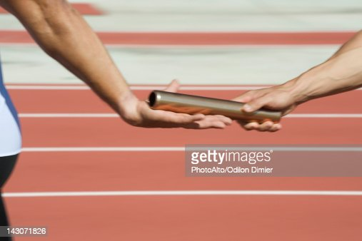 Runners exchanging baton in relay race, cropped