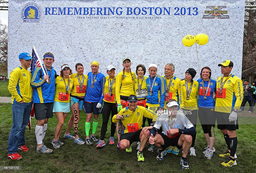 09 group pose for a picture in front of a banner signed by thousands of runners at the finish line at the Salt Lake City Marathon on April 20, 2013 in Salt Lake City, Utah. The group wanted to cross the finish line at the same time the bombs went off at the Boston Marathon in honor of those that were killed, injured, or not able to finish the race. Due to the bombings at the Boston Marathon on April 15, security was dramatically increased by law enforcement and Utah National Guard at the Salt Lake City Marathon. Organizers are asking spectators to leave backpacks at home.