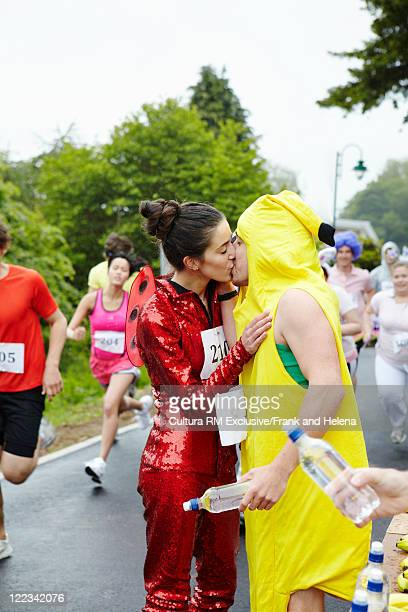 Runners in costume kissing in marathon
