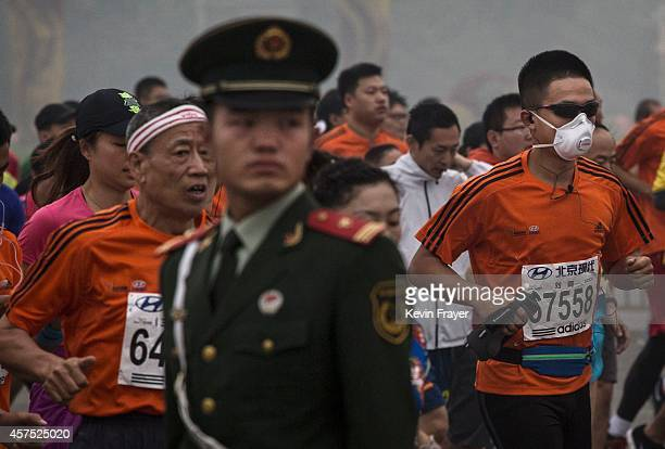 Runners in masks run past a soldier during the Beijing Marathon near Tiananmen Square October 19 2014 in Beijing China