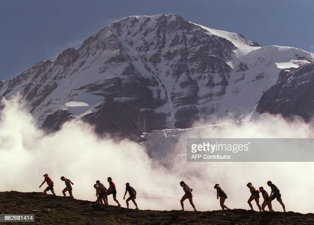 Runners in the annual Jungfrau Marathon held on the Eigergletscher mountain near Wengen are passed by low cloud as they take the final ascent in...