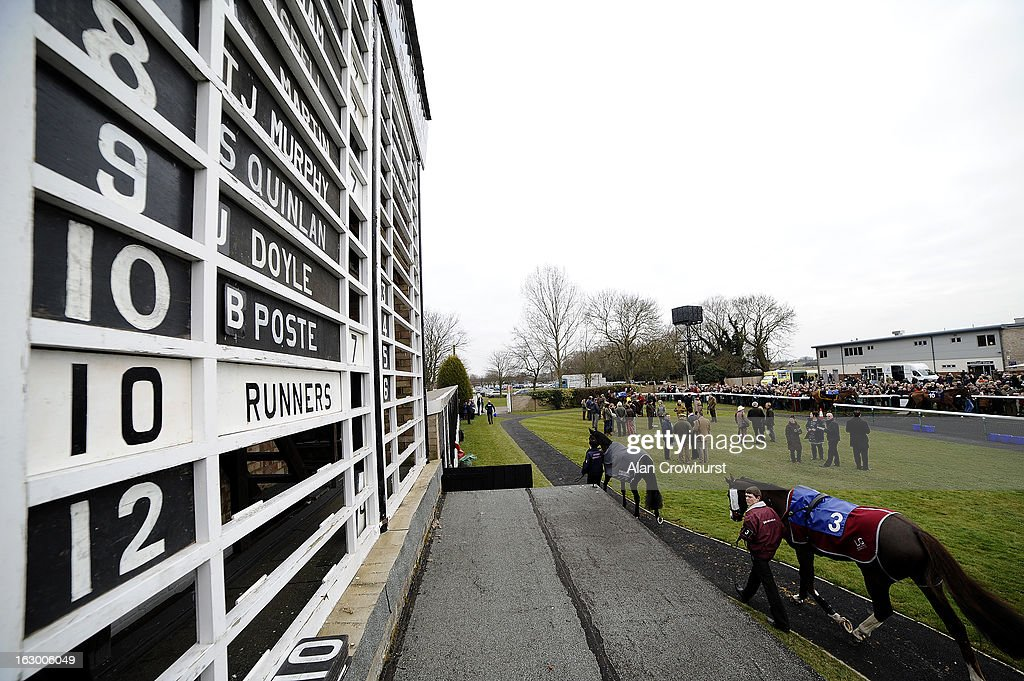 Runners in the parade ring make their way pass the runners and riders board at Huntingdon racecourse on March 03, 2013 in Huntingdon, England.