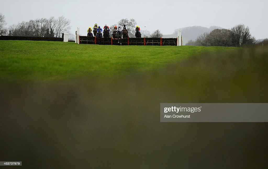 Runners in The Yeovil Town FC 'National Hunt' Novices' Handicap Hurdle Race take the flight in front of the stands at Wincanton racecourse on December 05, 2013 in Wincanton, England.
