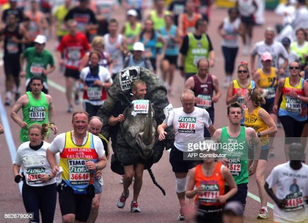 Runners including a man dressed up as a rhino approach the finish line at the end of the London Marathon 22 April 2007 Kenyan Martin Lel won the...