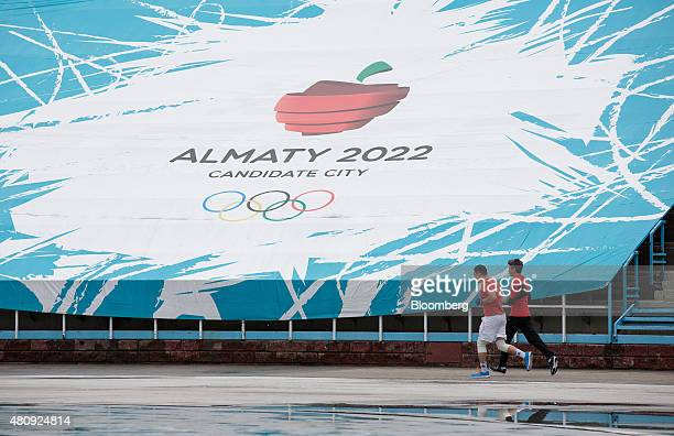 Runners jog past an advertisement for 'Almaty 2022' candidate city for the Winter Olympics as they train at the Medeo sports stadium in Almaty...