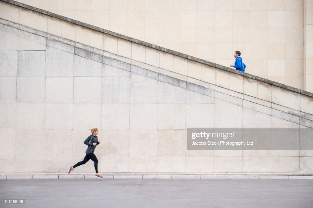 Caucasian runners jogging near staircase : Stock Photo