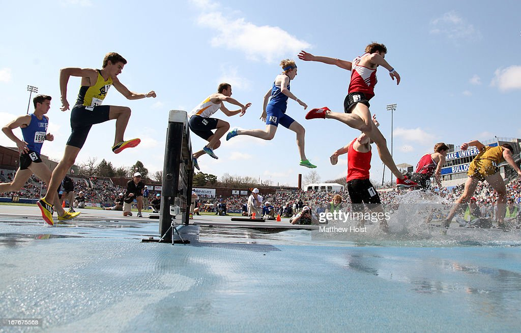 Runners jump over the water obstacle competing in the Men's 3000-meter Steeplehase at the Drake Relays, on April 27, 2013 at Drake Stadium, in Des Moines, Iowa.