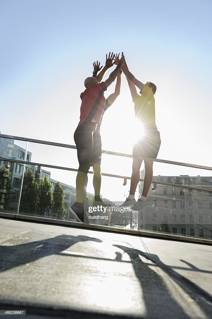 Runners jumping doing hi-five, Munich, Germany