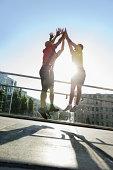 Runners jumping doing hi-five, Munich, Germany