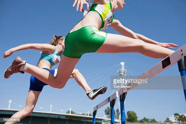 Runners jumping hurdles on track