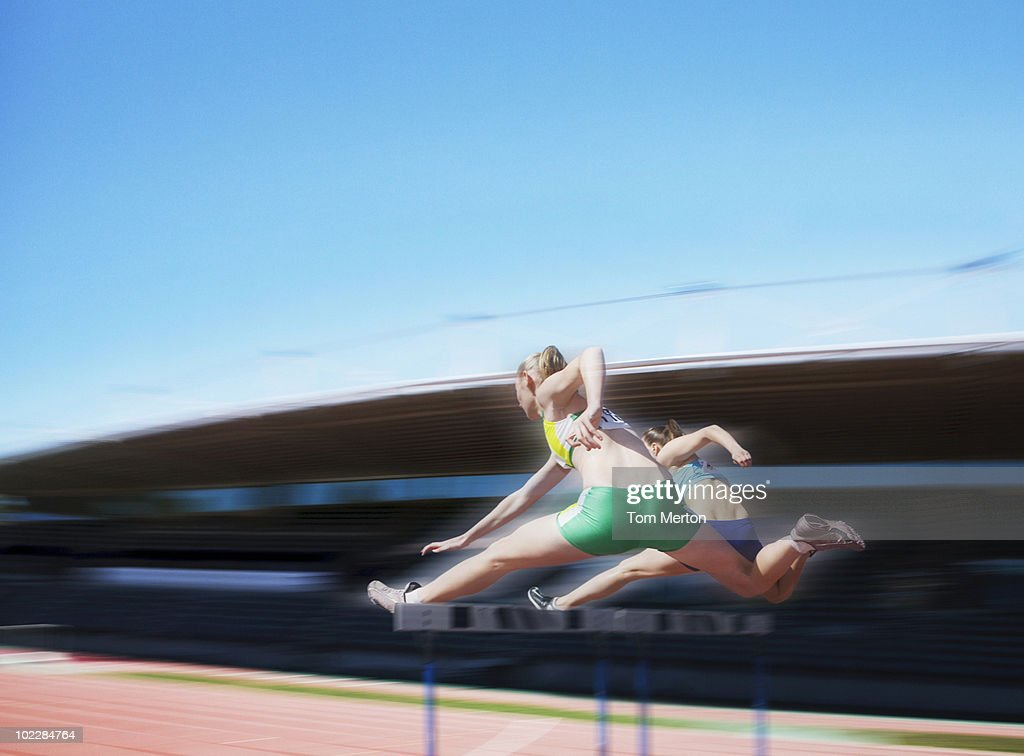 Runners jumping over hurdles : Stock Photo