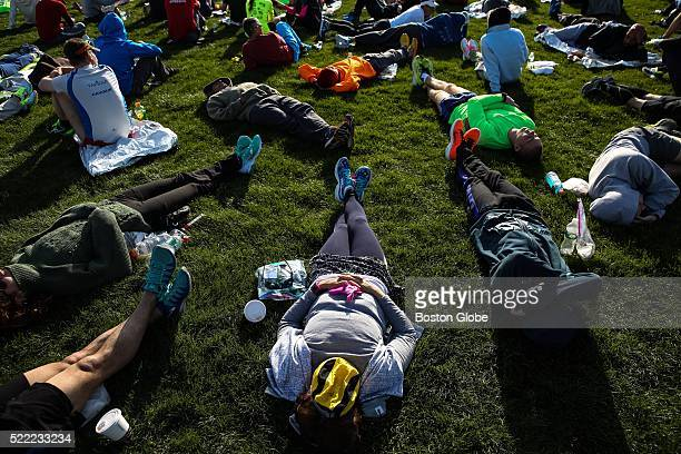 Runners lay in the grass at the Athletes' Village prior to the 120th Boston Marathon in Hopkinton Mass on April 18 2016