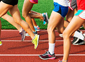 A girls cross country team running on a red track at the start of practice on a early summer evening.