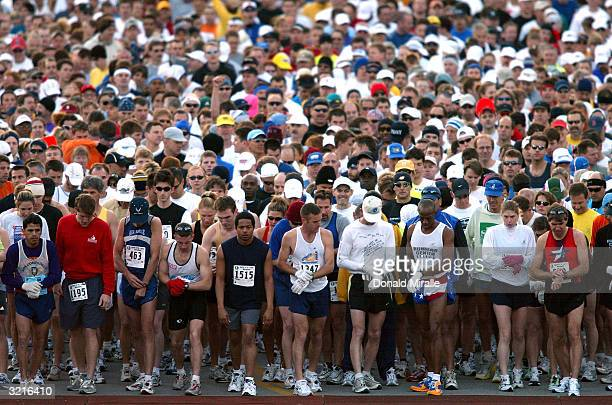 Runners line up for the start and set their watches during the 2004 Spirit of St Louis Marathon on April 4 2004 in St Louis Missouri